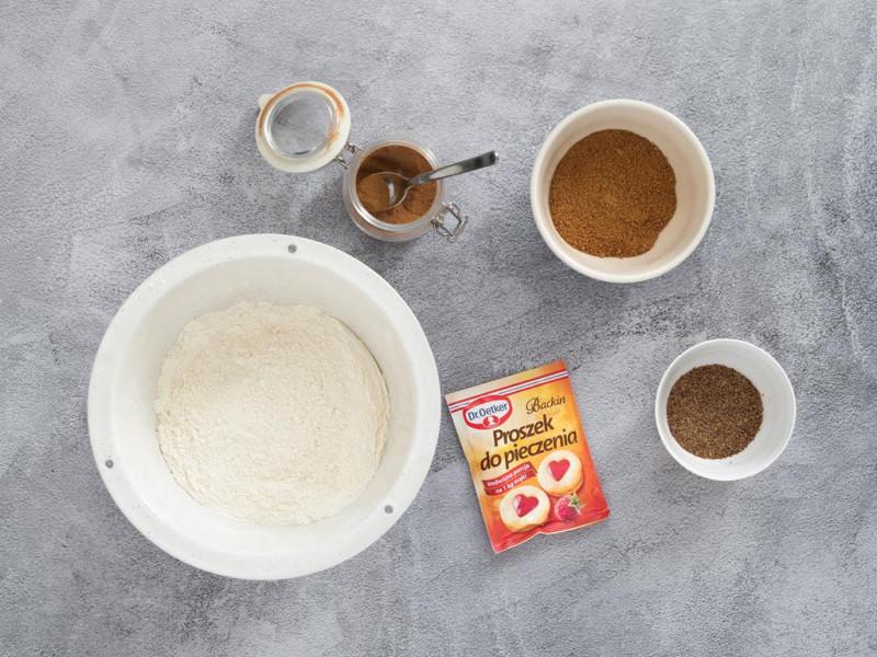 Mąka pszenna w misce, obok proszek do pieczenia Dr. Oetkera, mielony cynamon w słoiczku, zmielone siemię lniane oraz cukier kokosowy,