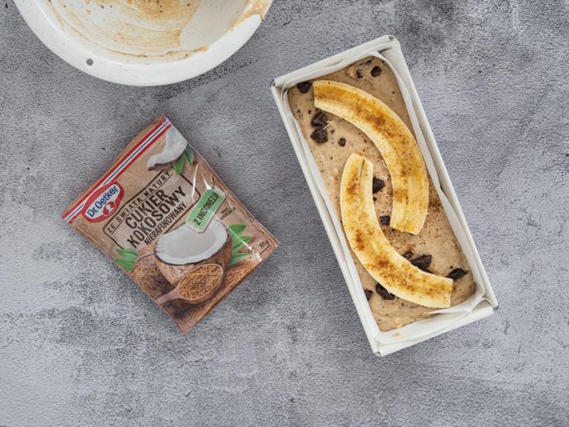 Ciasto na chlebek bananowy przełożone do keksówki. Ozdobione bananem i czekoladą. Obok cukier kokosowy Dr. Oetkera.