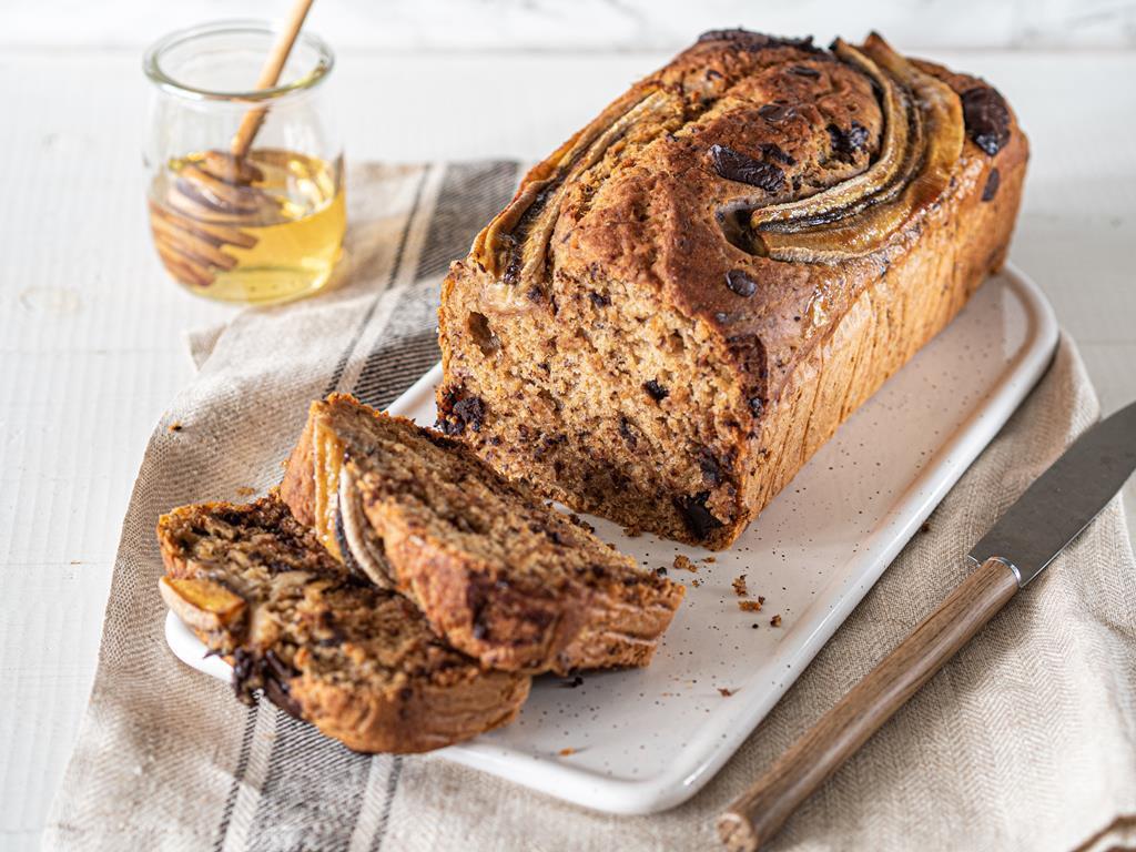 Wegański chlebek bananowy z czekoladą na białej desce- Wszystkiego Słodkiego