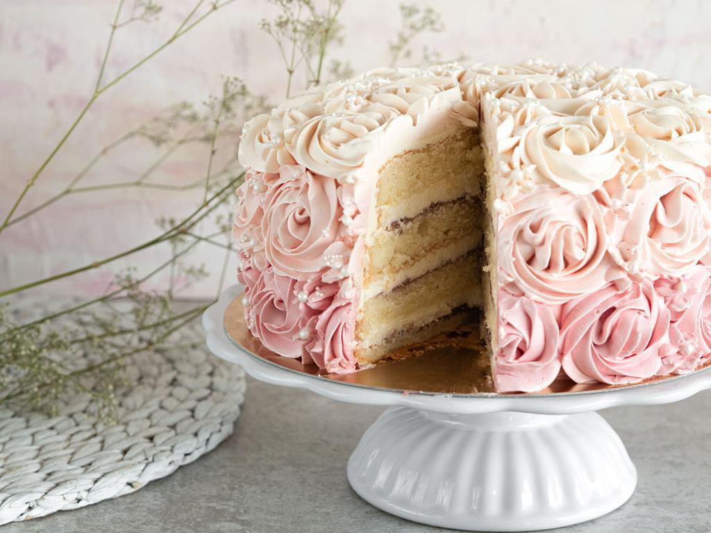 tort ombre z różami z kremu maślanego z wykrojonym kawałkiem ciasta