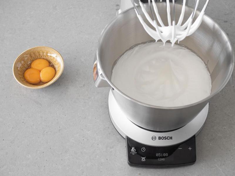 Ubite białka z cukrem w misie robota kuchennego MUM firmy Bosch. Obok żółtka w miseczce.