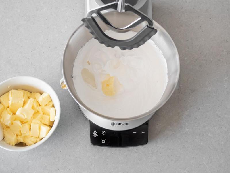 Pokrojone, miękkie masło z misce. Obok w misie robota kuchennego firmy Bosch ubita beza z kawałkami masła.