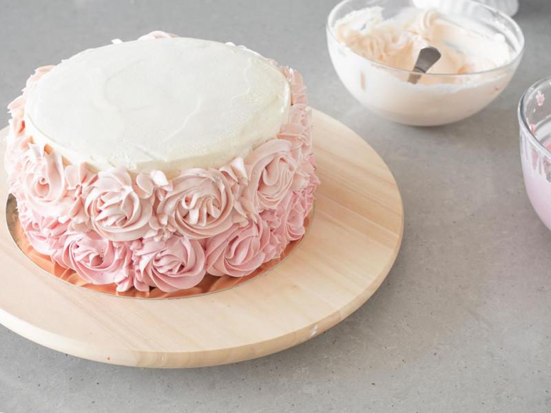 Tort w trakcie dekorowania różami z kremu maślanego w kolorze jasnoróżowym.