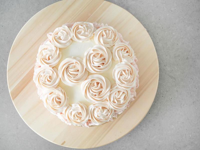 Tort udekorowany jasnymi różami z kremu maślanego.