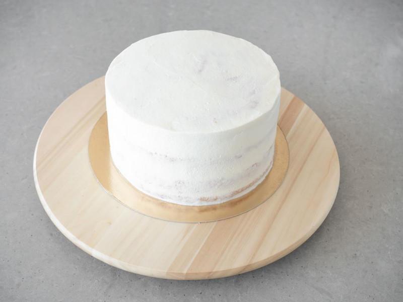Tort na drewnianej paterze pokryty kremem waniliowym.