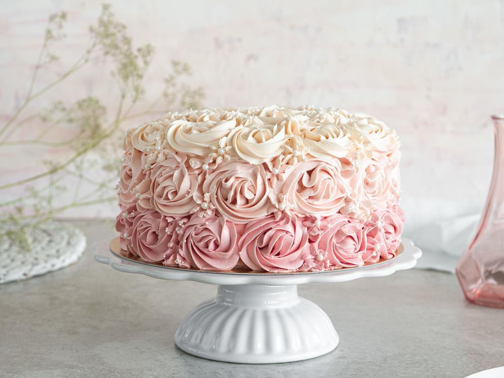 tort ombre z różami z kremu maślanego na białej ceramicznej paterze