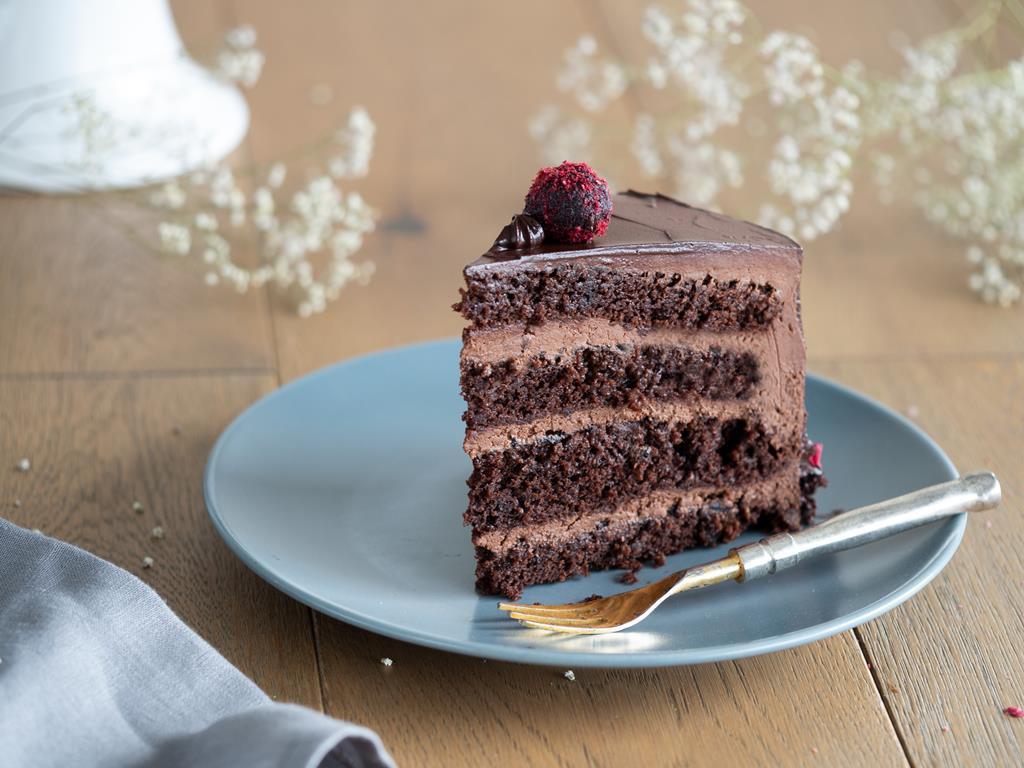 kawałek czekoladowego, wegańskiego tort na szarym talerzyku - Wszystkiego Słodkiego