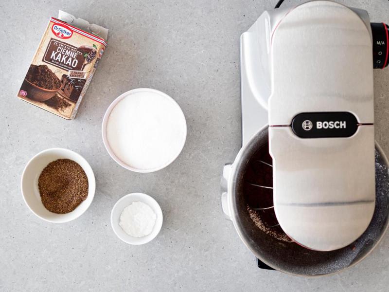 Robot kuchenny firmy Bosch,  a obok w miseczkach cukier, zmielone siemię lniane, proszek do pieczenia oraz ciemne kakao Dr. Oetkera.