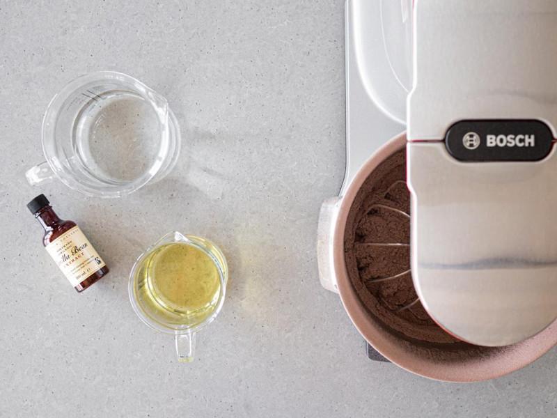 Ekstrakt waniliowy Taylor&Colledge, woda w dzbanku oraz olej i wymieszane suche składniki w misie robota kuchennego firmy Bosch.