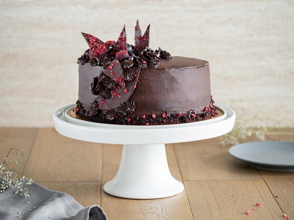 czekoladowy tort wegański z ozdobami z czekolady i liofilizowanymi malinami na bialej, ceramicznej paterze - Wszystkiego Słodkiego