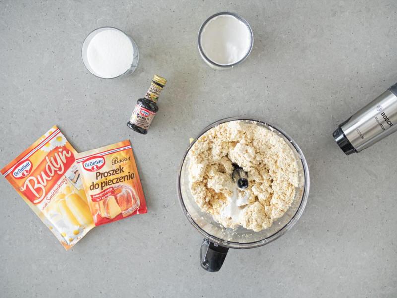 W malakserze tofu z sokiem z cytryny i skórką z cytryny, a obok ekstrakt z wanilii, mleko kokosowe, cukier, proszek do pieczenia i budyń.