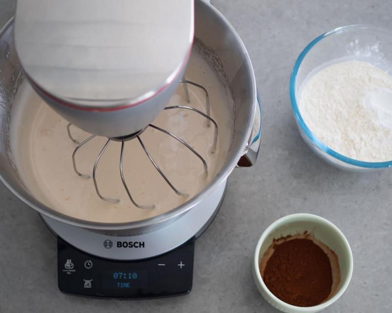 w robocie kuchennym bosch ubita masa jajeczna obok miseczka z ciemnym kakao Dr. Oetkera
