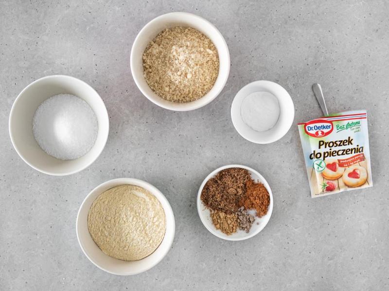 W miseczkach mąka jaglana, mielone migdały, ksylitol, przyprawy na talerzyku i proszek do pieczenia.