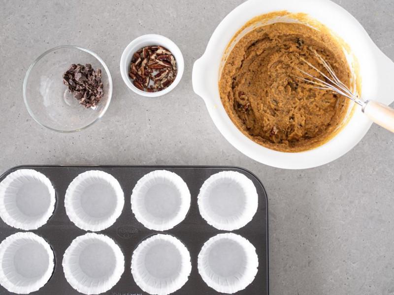 Ciasto na muffinki w misce. Obok blaszka na muffinki wyłożona papierem do pieczenia.