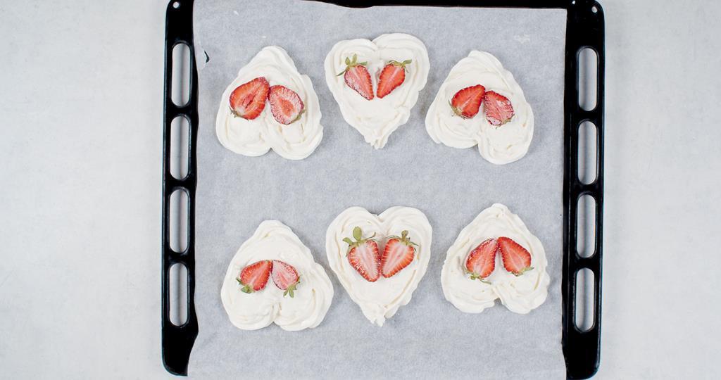 Upieczone bezy w kształcie serc udekorowane truskawkami