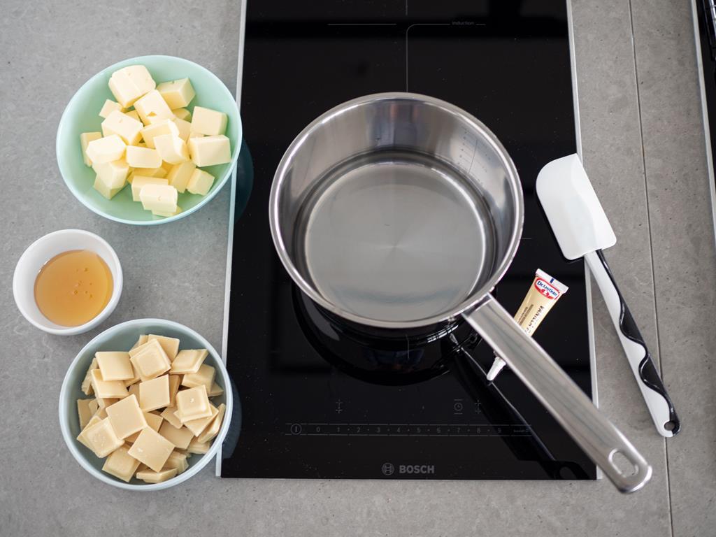 Na kuchence rondelek, w misce pokrojone masło, biała czekolada i miód