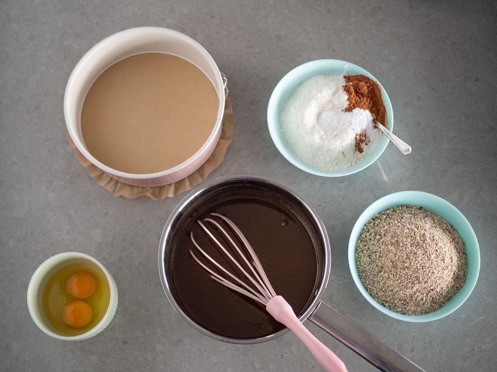 w rondelku ciasto kokosowe w miseczce tarte migdały oraz jajka