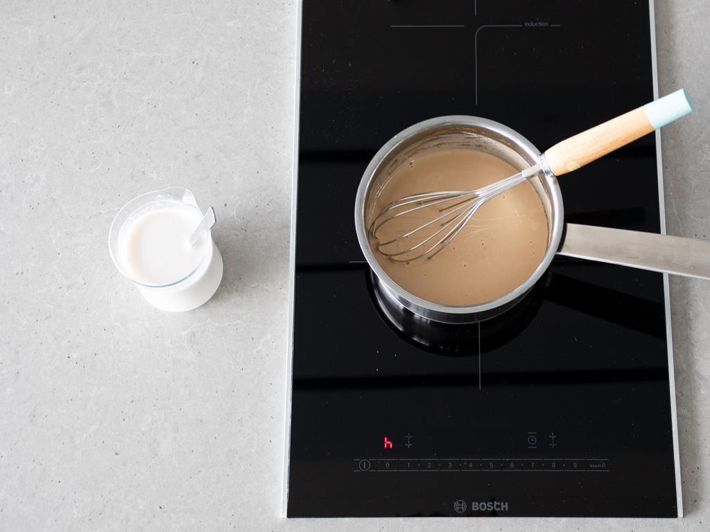 Rozmieszana skrobia z mlekiem migdałowym i ekstraktem z wanilii oraz garnek ze składnikami do puddingu wegańskiego.