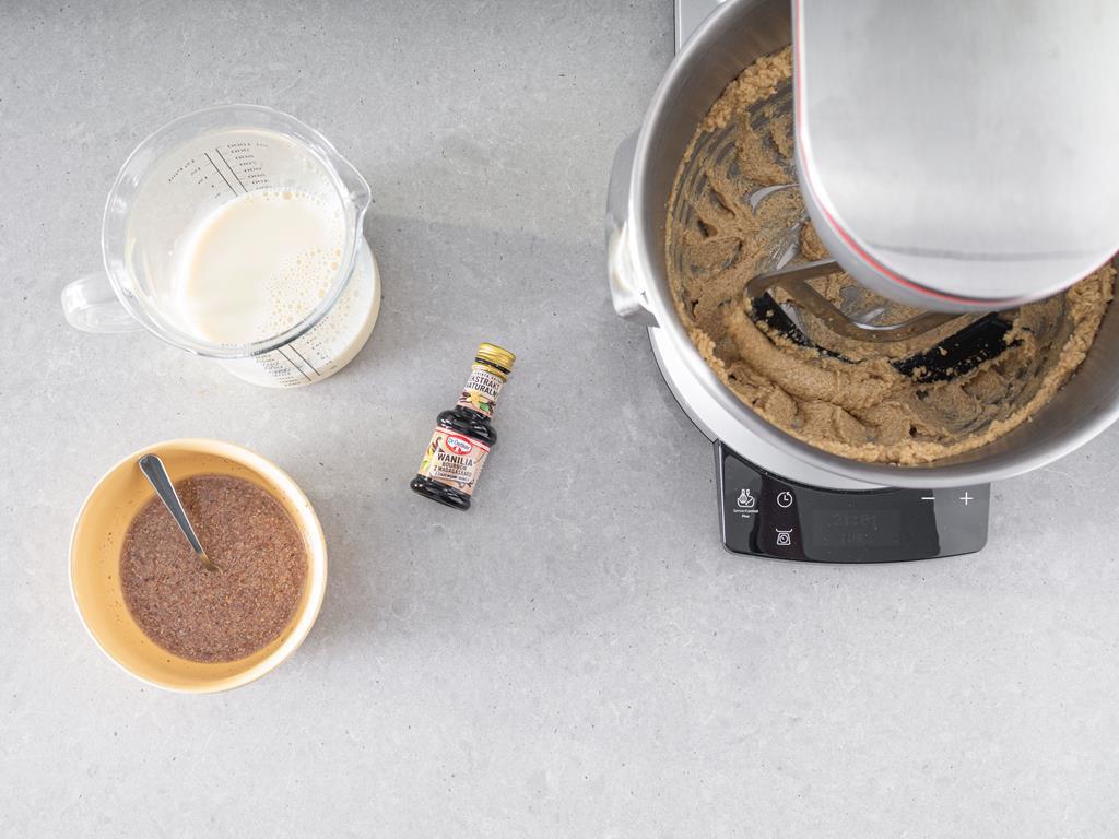 Utarte masło z cukrem, siemię lniane, mleko sojowe i ekstrakt waniliowy na blacie.