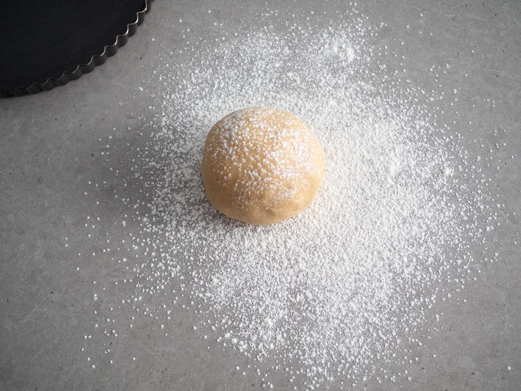 na blacie zagniecione kruche ciasto uformowane w kulkę