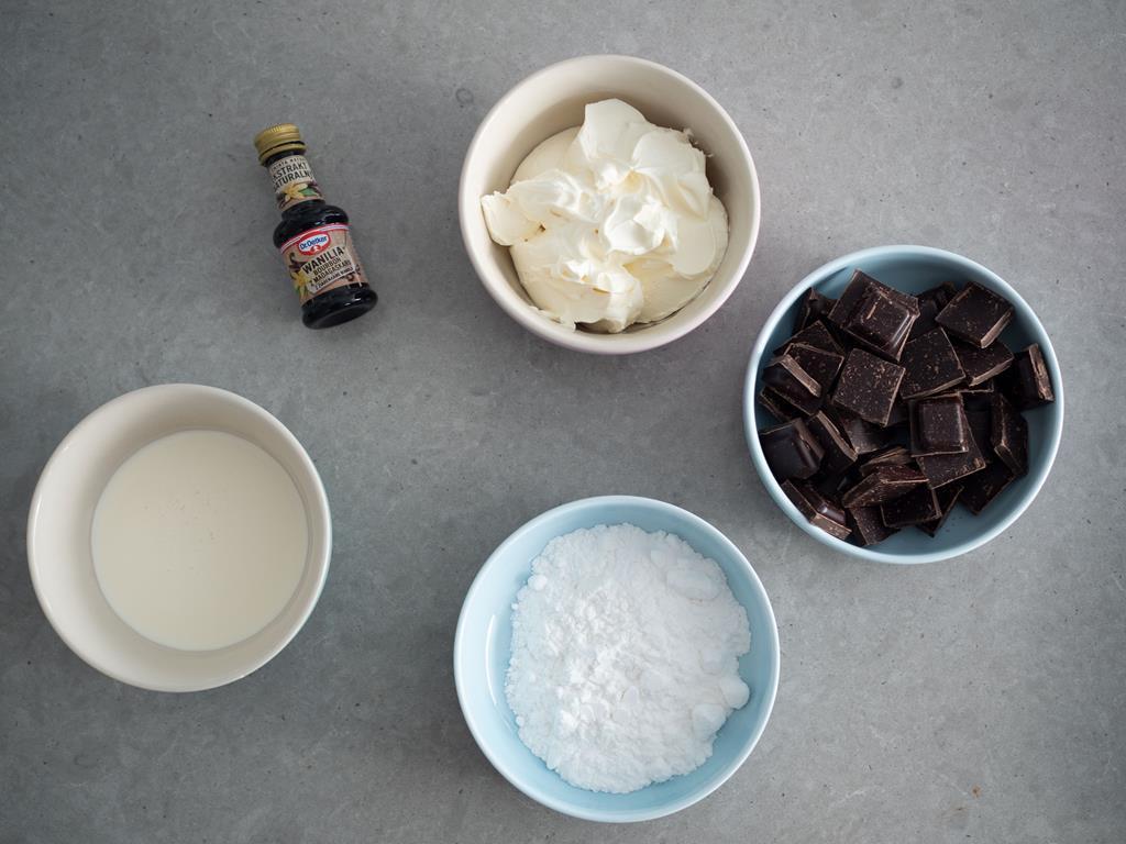 na stole miseczki z czekoladą, cukrem pudrem, śmietanką i serkiem mascarpone