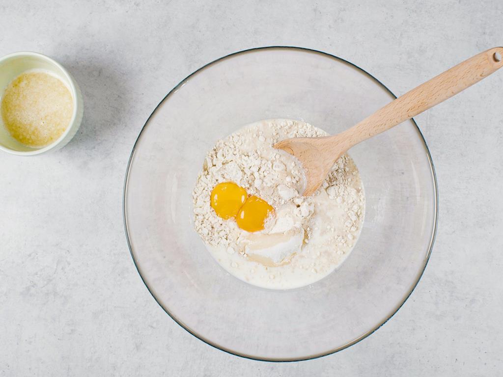 Wymieszana mąka, cukier, cukier wanilinowy, żółtka, mleko i rozpuszczone masło