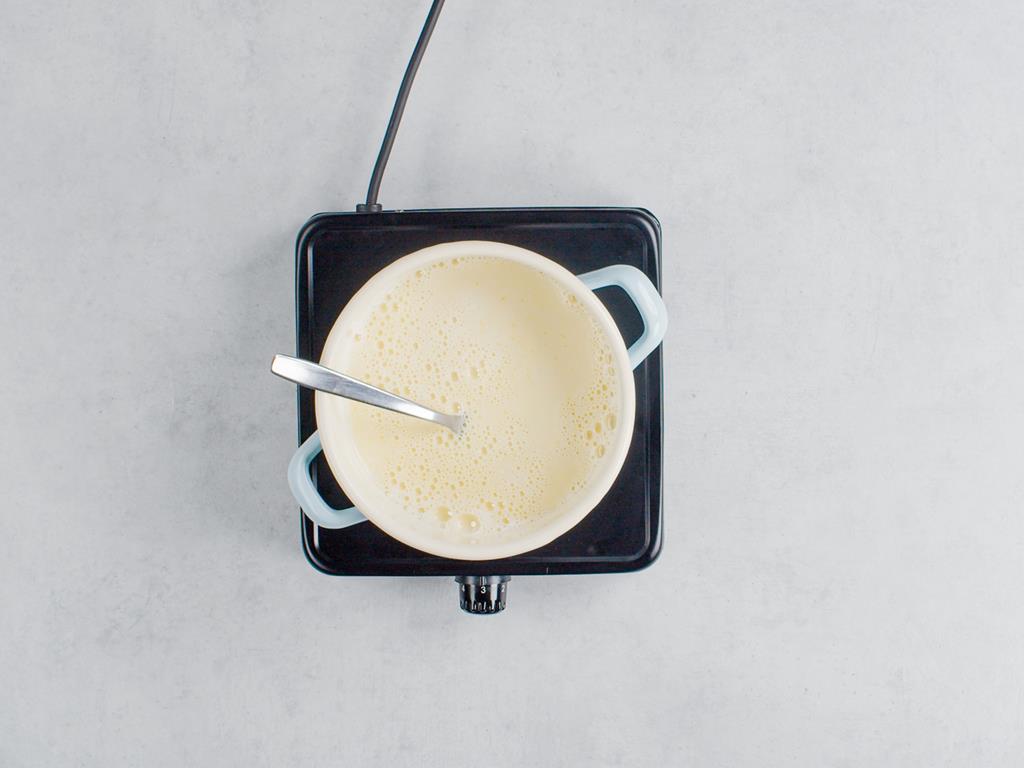 Gorące mleko gotujące się w garnuszku z budyniem