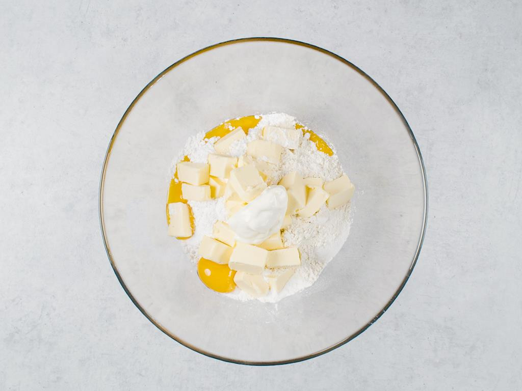 w szklanej misce mąka, żółtka, cukier i proszek do pieczenia