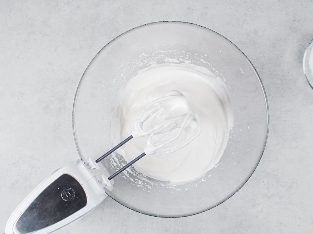 w szklanej misce ubite białka oraz miska z mąką ziemniaczaną