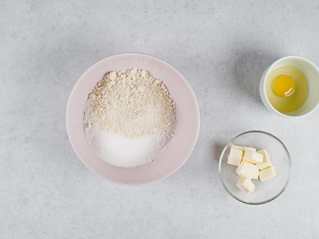 Mąka z migdałami, masło pokrojone w kostkę, jajko w miseczkach