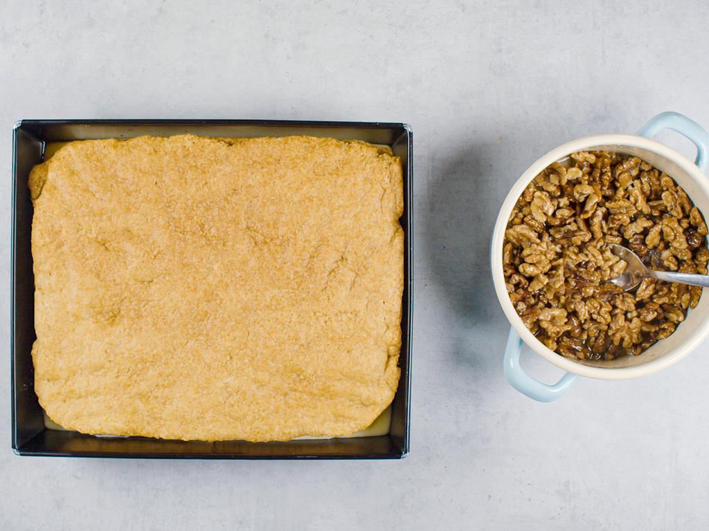forma z ciastem i miseczka z mieszanką orzechową