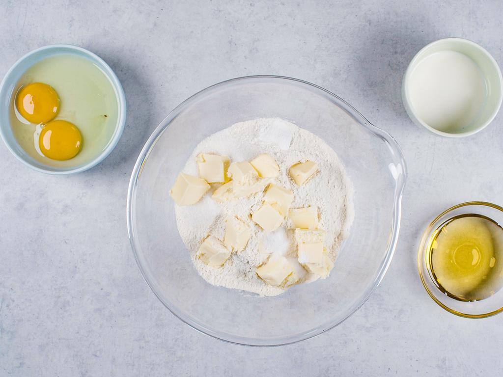 Mąka, cukier, proszek do pieczenia, soda, masło, jajka, miód i mleko w osobnych miseczkach