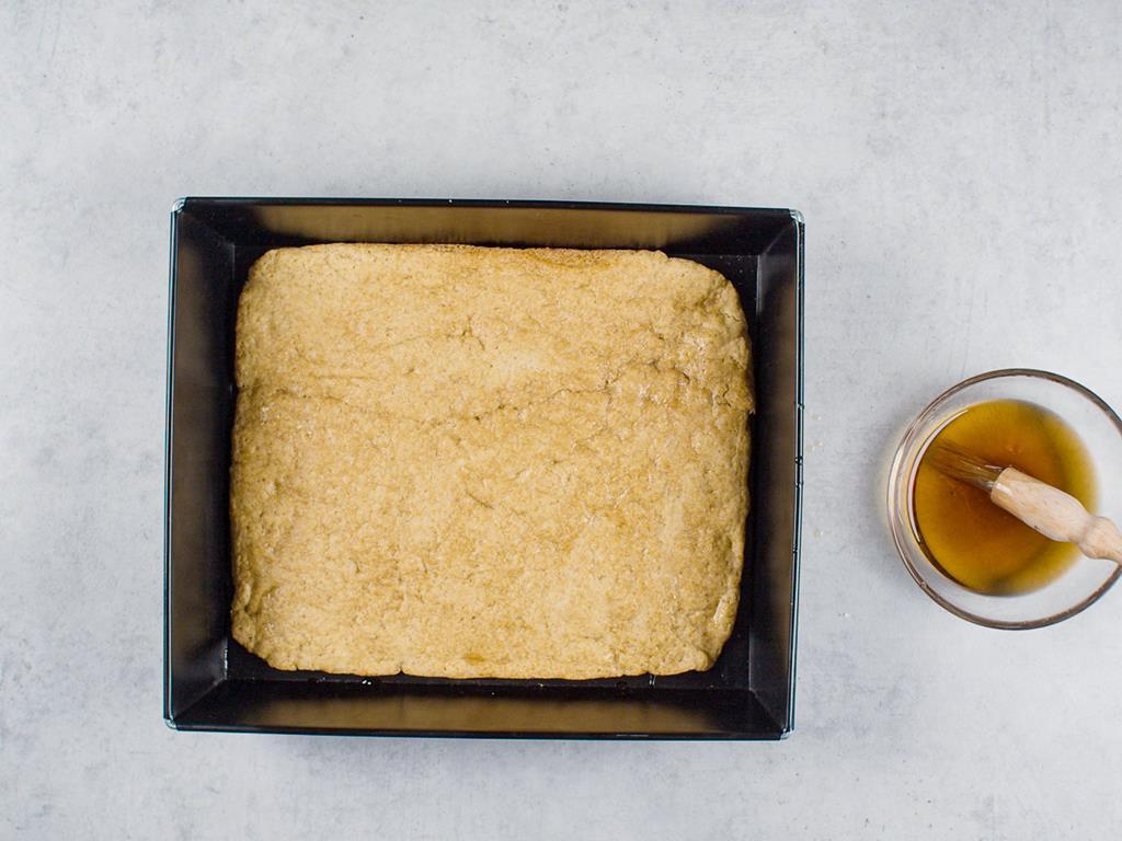 forma z upieczonym ciastem oraz miseczka z wódką orzechową