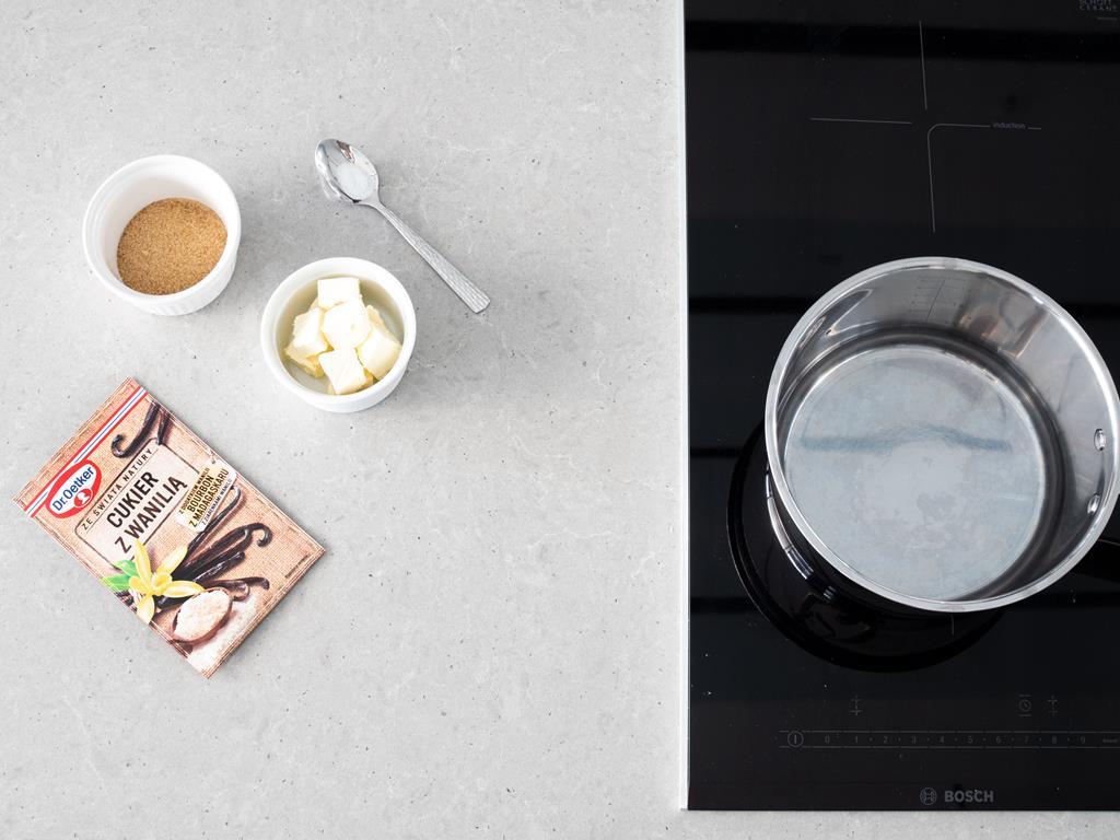 Cukier z wanilią, margaryna wegańska, cukier trzcinowy i szczypta soli. Obok na kuchence indukcyjnej woda.