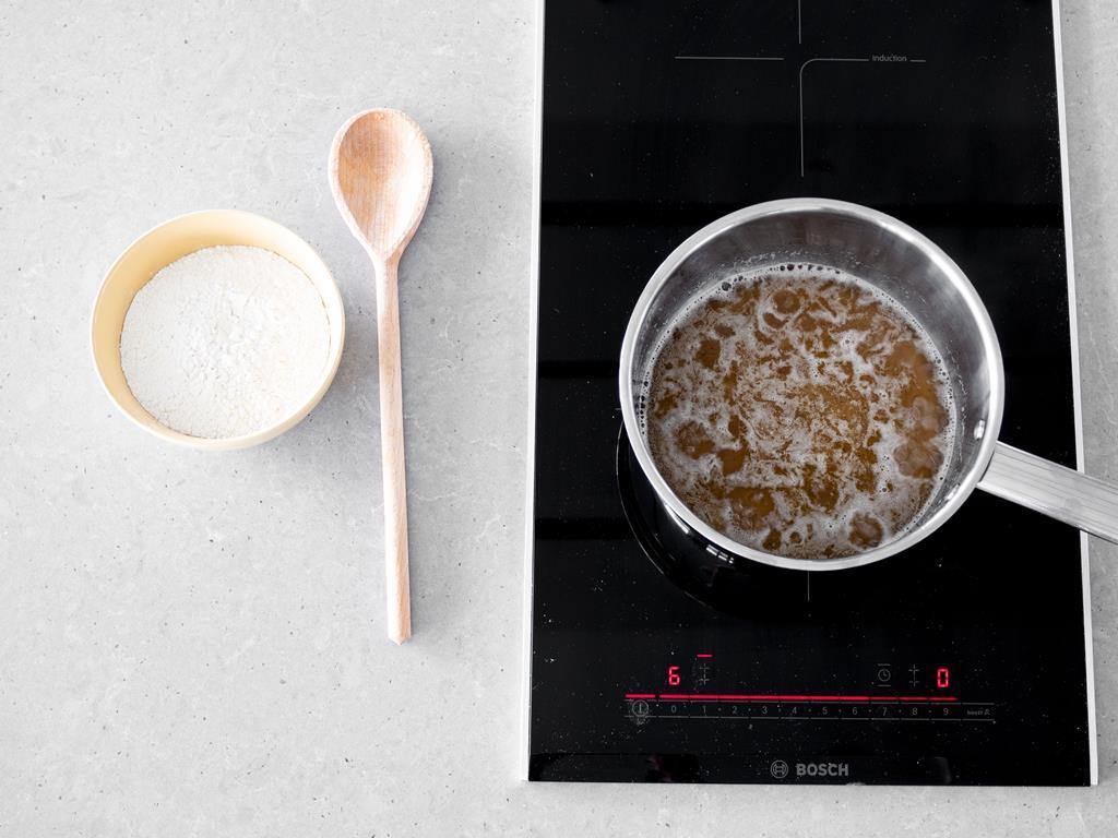 Na kuchence indukcyjnej Bosch, gotująca się woda, z cukrem trzcinowym, cukrem z wanilią, margaryną wegańską i wodą. Obok w miseczce mąka i drewniana łyżka.