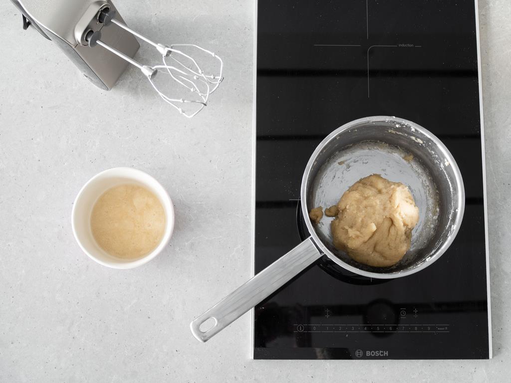 Aquafaba w miseczce oraz zaparzone ciasto wegańskie. Obok mikser ręczny firmy Bosch.