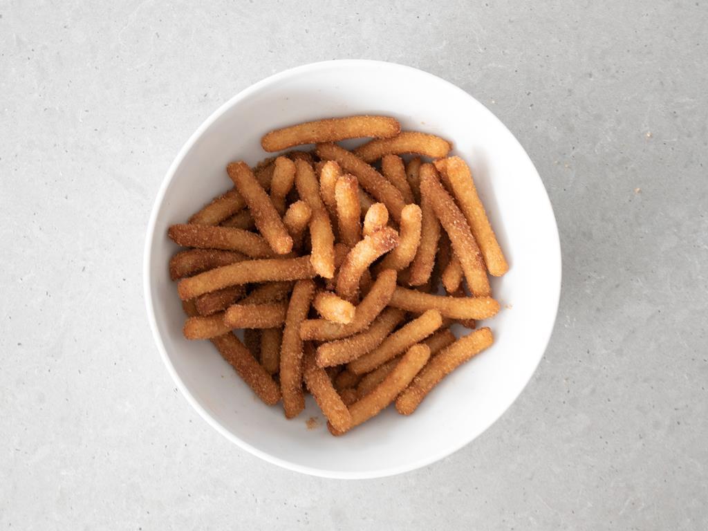 Obtoczone churros w cukrze z cynamonem.