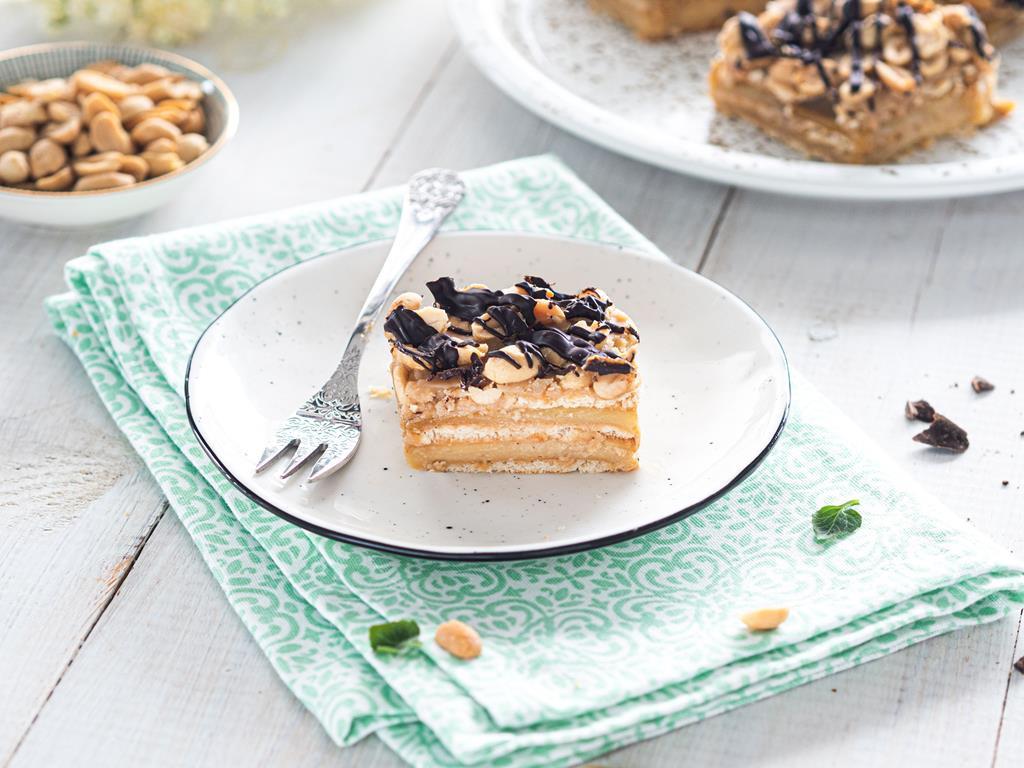 ciasto snikers bez pieczenia z czekoladą i orzechami ziemnymi na białym talerzyku