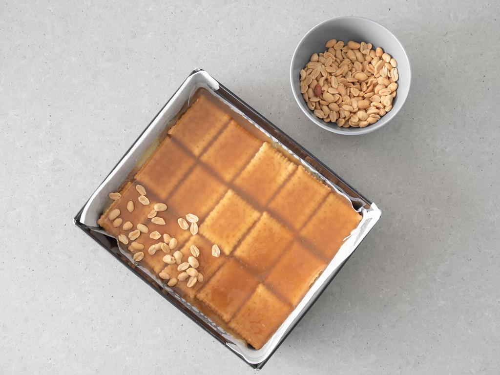 Ostatnia warstwa herbatników polana wegańskim kajmakiem i posypana solonymi orzeszkami ziemnymi.
