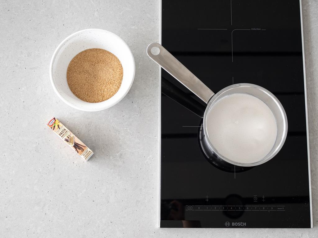 Przygotowywanie wegańskie kajmaku. W miseczce cukier trzcinowy, obok pasta z wanilii Dr. Oetker. W garnku mleko kokosowe, na płycie indukcyjnej Bosch.