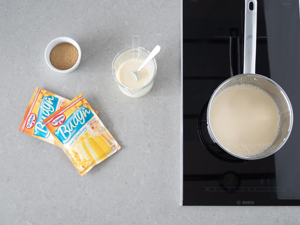 Przygotowanie wegańskiego budyniu. Na blacie budynie waniliowe firmy Dr. Oetker, mleko sojowe oraz cukier trzcinowy. W garnku na płycie indukcyjnej podgrzewana cześć mleka sojowego.