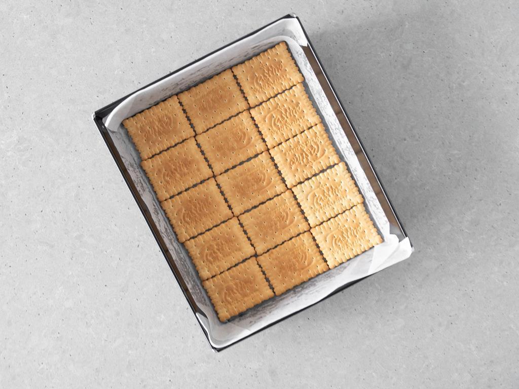 Forma do pieczenia wyłożona pierwszą warstwą herbatników.