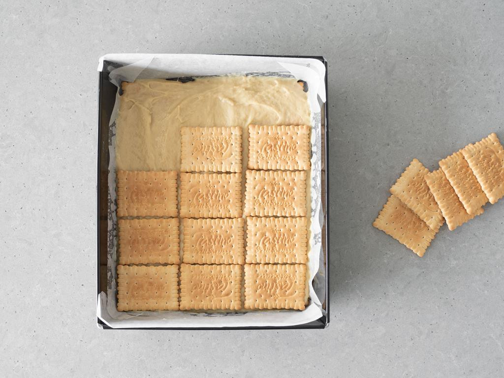 Rozsmarowany krem budyniowy z dodatkiem masła orzechowego na pierwszej warstwie herbatników.