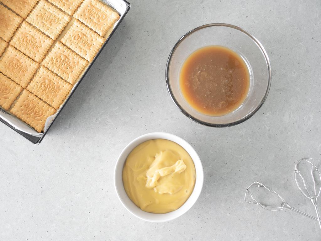 Na blacie w miseczce przygotowany budyń, a w drugiej misce kajmak wegański.