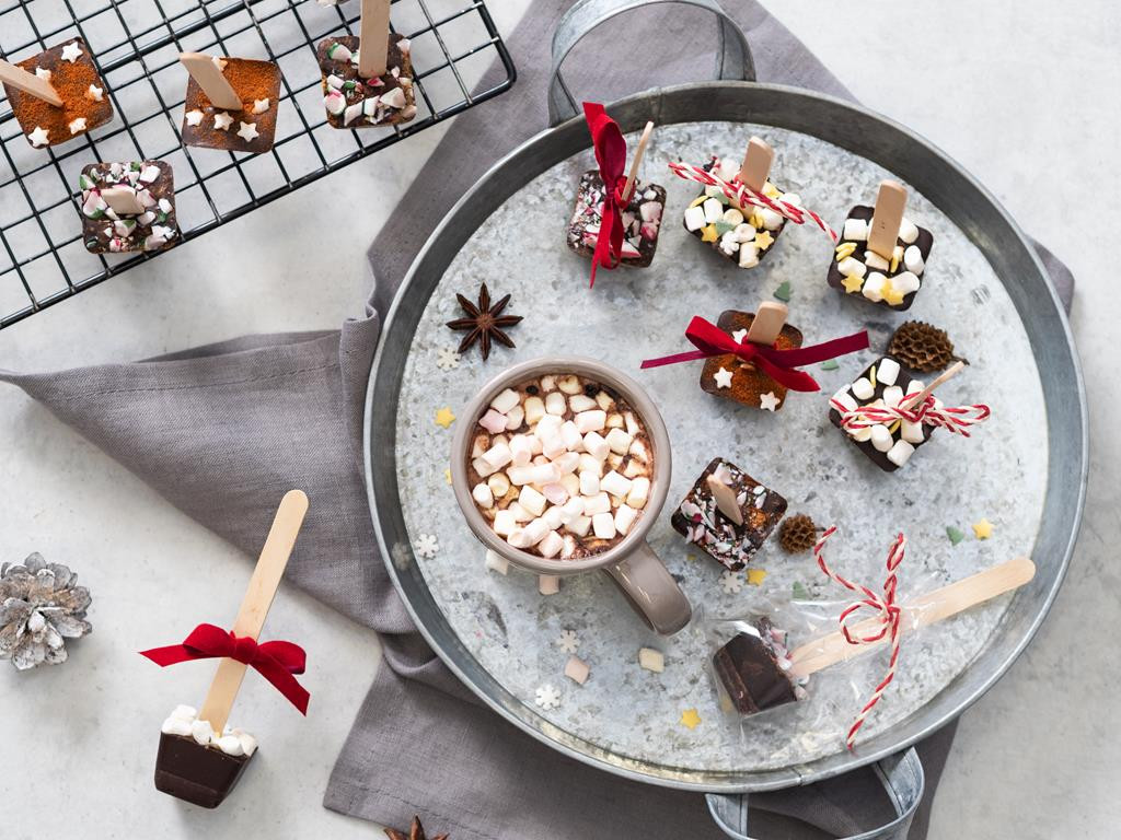 Gorąca czekolada na patyku z cynamonem, chili i piankami. Czekoladki ułożone na tacy, obok czekolada na gorąco z piankami.