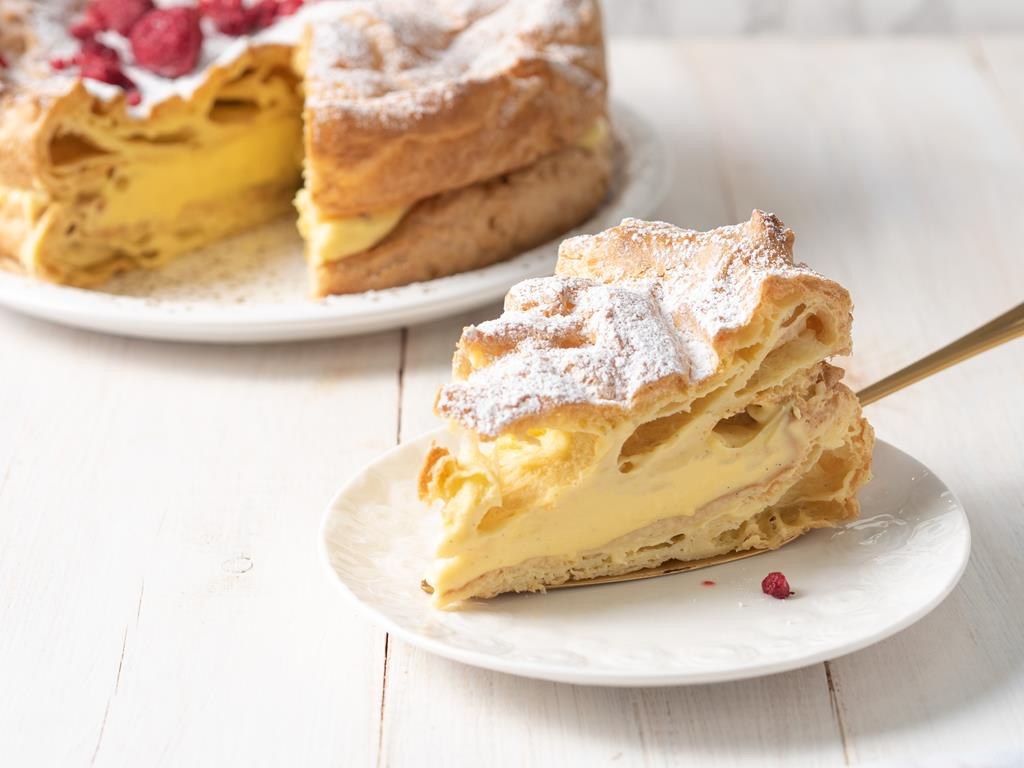 kawałek ciasta karpatkowego z kremem budyniowym oprószony cukrem pudrem