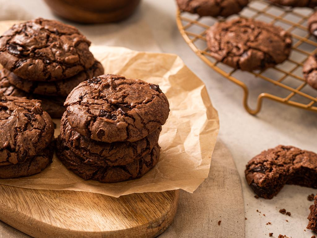 Wegańskie czekoladowe ciasteczka z dodatkiem chili i kawałkami czekolady na drewnianej desce.