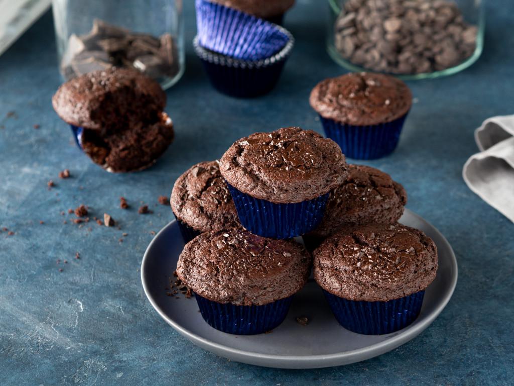 Czekoladowe muffinki z kawałkami czekolady w metalicznych papilotkach na szarym talerzyku.