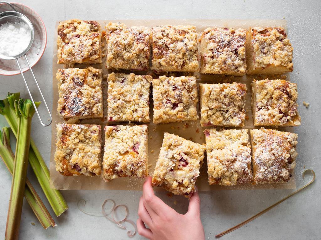 Drożdżówka pokrojona na kawałki z serem i rabarbarem, łodygi rabarbaru leżące obok ciasta