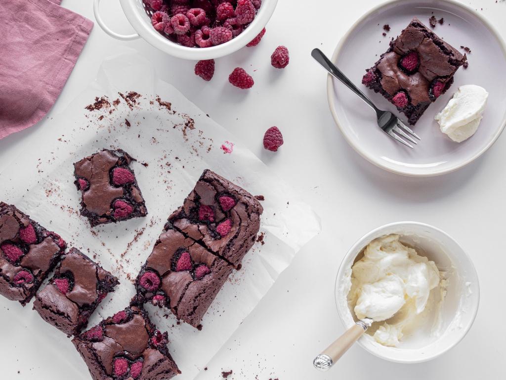 brownie z malinami na papierze i na talerzyku serwowane z kremem śmietankowym -wszystkiego słodkiego